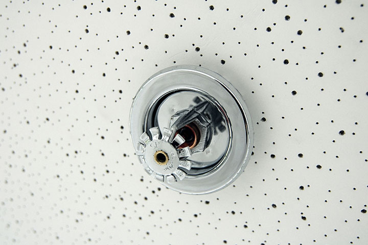 a fire sprinkler head mounted in an acoustic tile ceiling